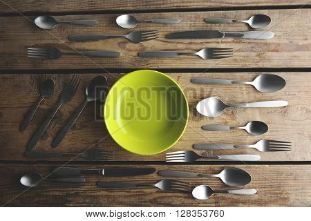 Plate and silver cutlery on wooden table, top view