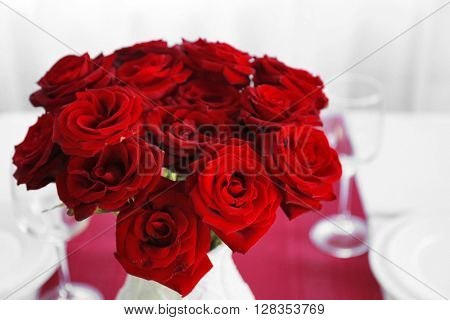 Vase with red roses on a holiday served table, closeup