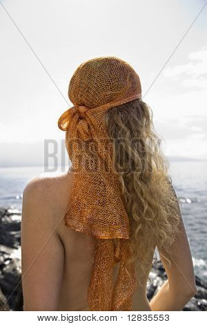 Back view of nude Caucasian mid-adult woman with wavy hair and head scarf at coast.