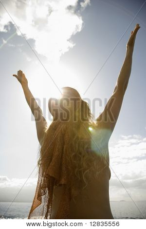 Back view of nude Caucasian mid-adult woman with head scarf at coast raising arms to sky.