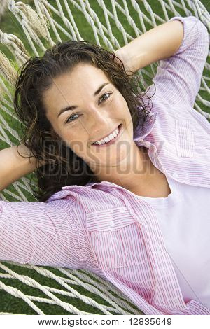 Pretty young adult Caucasian brunette female lying in hammock with hands behind head smiling at viewer.