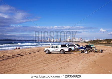 Vehicles On Beach Against City Skyline Durban South Africa