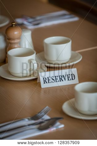 Wine glasses, coffee cups and cutlery on the table reserved by customers before the start of the service in the restaurant