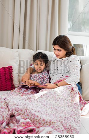 Mother and daughter sitting on sofa and reading book together