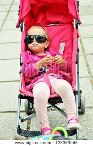 cute baby girl sitting in the stroller