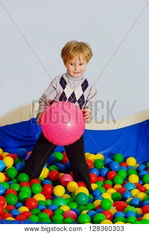 little boy playing in playground colorful ball pool