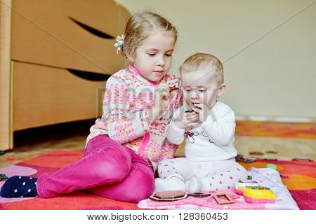 little girl and baby girl playing on the carpet