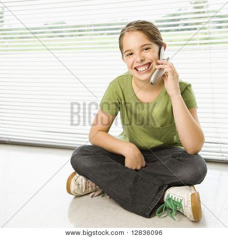 Caucasian preteen Mädchen sitzen auf Boden am Handy sprechen und lächelnd auf Betrachter.