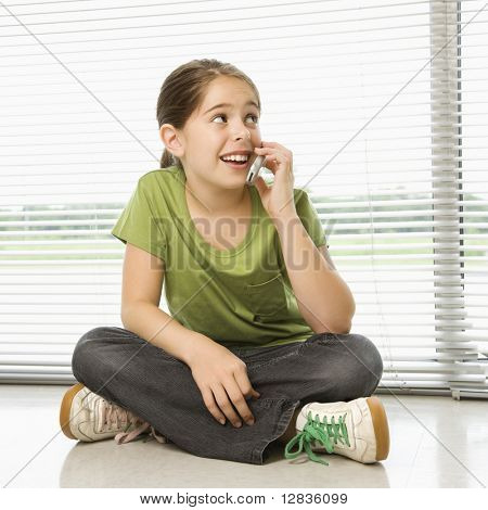 Caucasian preteen Mädchen sitzen auf Boden am Handy sprechen.