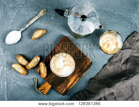 Glasses of coffee with ice cream on rustic wooden board, steel Italian Moka pot over grey concrete textured background, top view