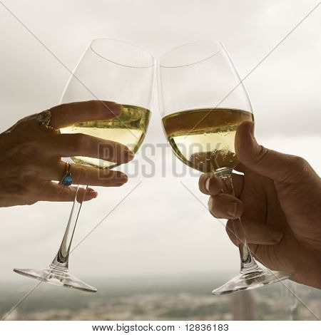Close up of mature couple's hands toasting white wine.