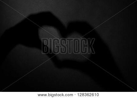 Hand shaped heart on dark background