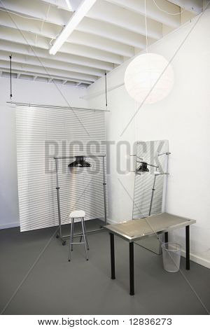 Workspace with table, chair, mirror, clothing rack and room divider.
