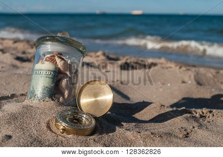 glass jar with money and old gold compass lying in the sand on the beach