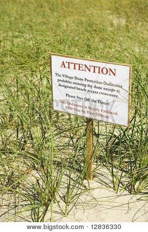 Sign warning visitors not to walk on or disturb natural dune area.