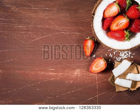 Half coconut with strawberries and wedges of coconut and shredded coconut on dark wooden background. Copy space