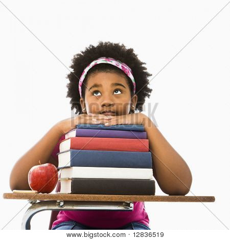 African American girl sitting in school desk with large stack of books looking bored.