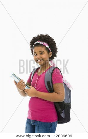 African American girl holding books and wearing backpack smiling at viewer.