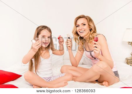 Cheerful Woman And Her Girl Kid Holding Different Varnishes For Nails