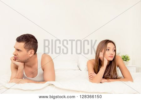 Portrait Of Man And Woman Lying Unhappy In Bed After Quarrel