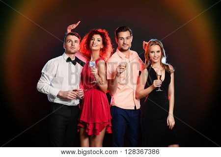 Cheerful young people dancing in a party club and drinking champagne. Holidays, celebration.