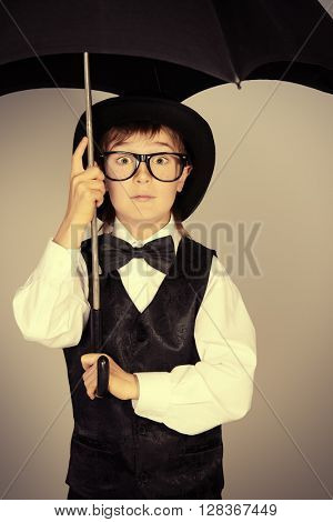 Cute boy in elegant suit, bowler hat and glasses standing under the umbrella. Children fashion. Studio shot.