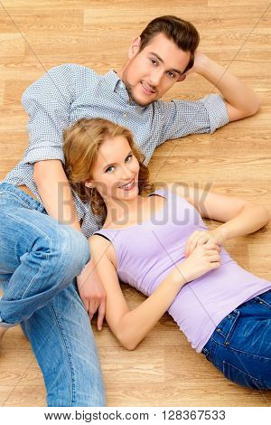 Happy couple lying together on a floor at home. Moving to a new home. Apartment repair.