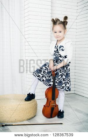 little girl with a violin and bow looking at camera