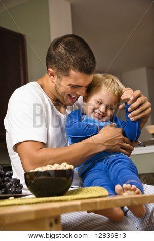 Caucasian man tickling toddler son in kitchen.