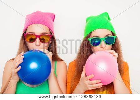 Portrait Of Two Girls In Hats And  Spectacles Blowing Balloons