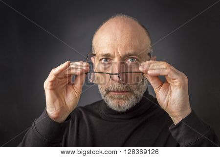 look over reading glasses - headshot of  60 years old  man with a beard against a black background