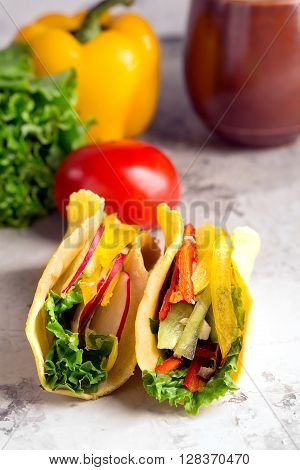 Taco with fresh vegetables on a grey surface
