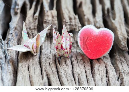 Origami couple paper crane and heart on wood