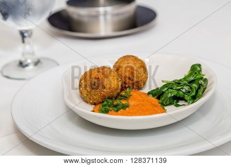 Conch Fritters and Wilted Spinach with spicy sauce