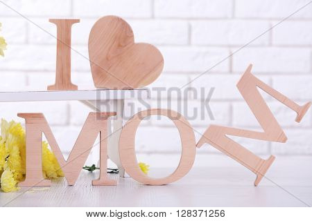 Wooden decor and flowers for mother's day on brick wall background