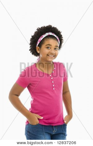 African American girl with hands in pockets wearing headband smiling at viewer.