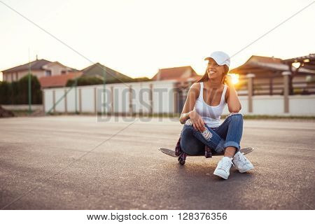 Woman having a break while enjoying skating in the city.