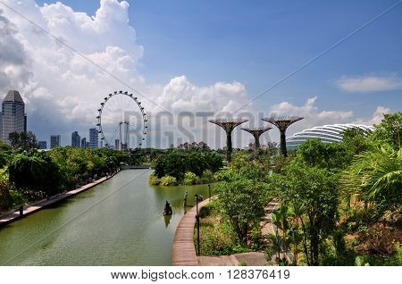 SINGAPORE - MAY 11, 2014: The view of Singapore Flyer and group of artificial trees are located around the water where called - Gardens by the Bay. There are many tourists come to visit everyday.