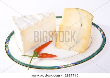 Two cuts of French cheese with red chili peppers