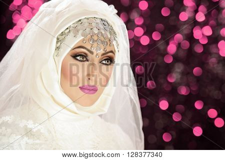 Portrait of a beautiful asian indian model in bridal costume and traditional jewellery and makeup