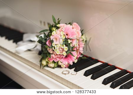 wedding bouquet of flowers on the piano keyboard with wedding rings