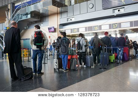 VALENCIA, SPAIN - APRIL 30, 2016: Airline passengers checking in at an airline counter in the Valencia Airport. About 4.98 million passengers passed through the airport in 2015.