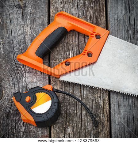 Handsaw And  Measuring Tape On A Wooden Board