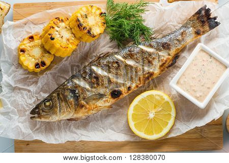 fish baked on the grill. with potatoes and lemon. sauce in bowl