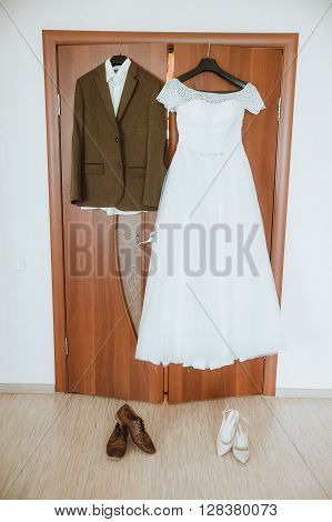 bride dress and groom's suit on a hanger hanging in the room on the door