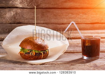 Burger on stick and cola. Glass of cola and hamburger. Hot food with cool drink. Simple snack at local bistro.