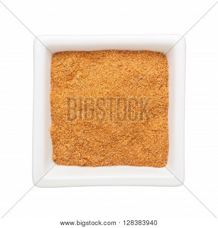 Curry powder in a square bowl isolated on white background