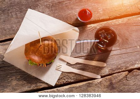 Burger with cutlery and ketchup. Hamburger and glass with cola. Traditional burger with special sauce. Lunch from bistro's menu.