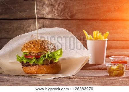 Burger on paper and fries. Table with beefburger and fries. Sliced pickles and fast food. High-calorie lunch at restaurant.