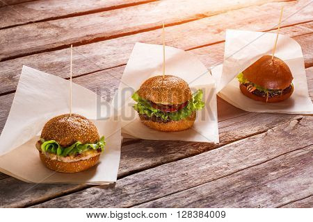 Hamburgers on white wrappers. Old wooden table with burgers. Juicy lettuce and warm buns. Savoury burgers in local bistro.